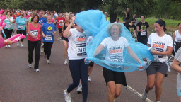 A groups of people running with one woman wearing a mosquito net