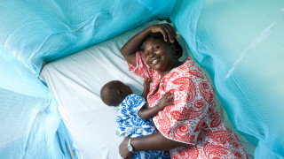 A woman and her child under a mosquito net