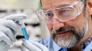 Bearded male scientist in goggles looking at a test tube in a lab