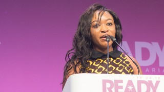 Ndifanji giving a speech at the lectern at the Malaria Summit London 2018