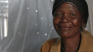 An older lady sitting in front of a mosquito net