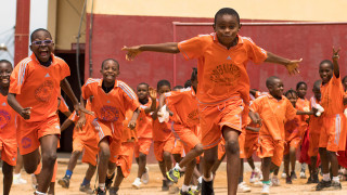 Children in a Cameroon school playground running towards the camera laughing