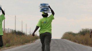 Women walking down a dusty road holding packages on their heads