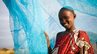 A child smiling in front of a mosquito net outside