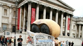 Someone in a mosquito costume reading the newspaper in Trafalger Square London